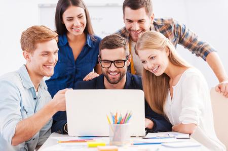 Brainstorm. Groep van vrolijke mensen uit het bedrijfsleven in smart casual kleding te kijken naar de laptop bij elkaar en glimlachen