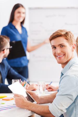 reunion de trabajo: Feliz de ser parte de un gran equipo. Hombre joven confidente que sostiene la tablilla digital y sonriendo mientras que la mujer de pie en el fondo y se�alando la pizarra Foto de archivo