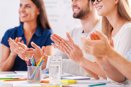 Good job! Cropped image of happy business people in smart casual wear sitting together at the table and applauding to someone
