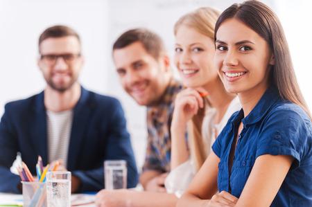 我々 は信頼できるチームです。スマートのカジュアルな服装のテーブルで一緒に座っていると笑顔で自信を持ってビジネス人々 のグループ 写真素材