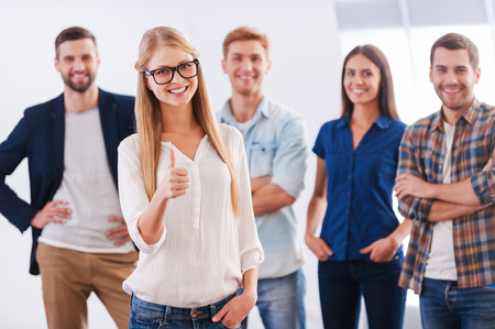 Join a successful team! Beautiful young woman showing her thumb up and smiling while group of happy young people standing  Standard-Bild