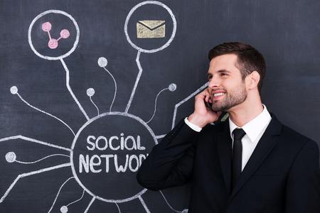 vie sociale: Vie sociale active. Beau jeune homme parle au t�l�phone tout debout contre le r�seau social dessin � la craie sur le tableau noir