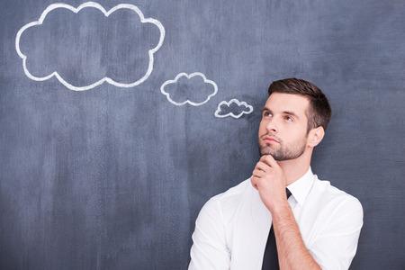 Fliegen von Gedanken. Durchdachter junger Mann mit der Hand am Kinn und Wegschauen im Stehen vor Wolke Kreidezeichnung auf Tafel