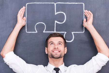 Good strategy - good solution. Handsome young man keeping arms raised and connecting jigsaw pieces on blackboard photo