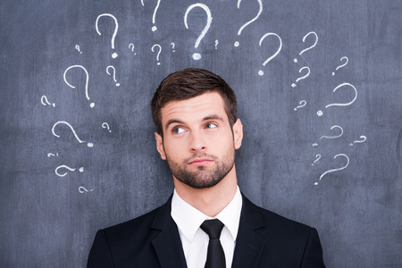 so: So many questions! Confused young man standing against blackboard with question marks