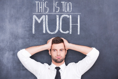 Just can not stand! Confused young man standing against chalkboard with hands on his head photo