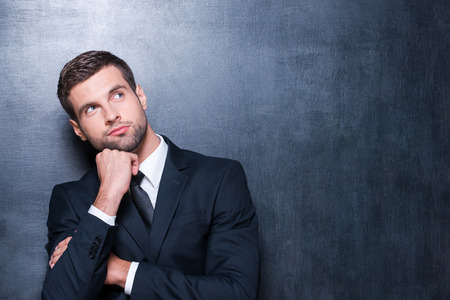 Thoughtful businessman. Handsome young man in shirt and tie looking away and holding hand on chin while standing against blackboard