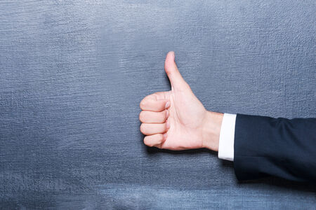 stand up: Good job! Close-up of man showing thumb up against blackboard