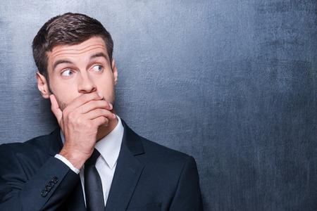 mouth: De ninguna manera! Hombre joven dado una sacudida el�ctrica en formalwear que cubre la boca con la mano y mirando a otro lado mientras est� de pie contra la pizarra Foto de archivo