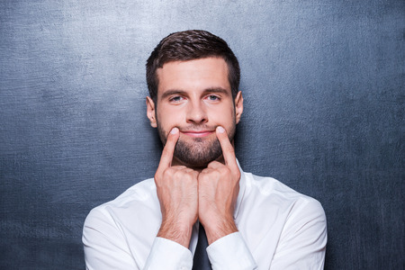 fake smile: Put on your smile! Handsome young man in formalwear holding fingers on his mouth and making fake smile while standing against blackboard Stock Photo