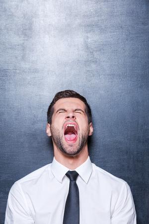 boca cerrada: Hombre de negocios furioso. Hombre joven furioso en camisa y corbata gritando y mantener los ojos cerrados mientras está de pie contra la pizarra