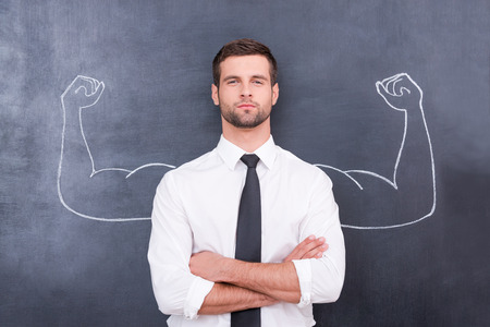 strength: Hidden possibilities. Handsome young man in shirt and tie looking at camera and keeping arms crossed while standing against chalk drawing of muscular arms