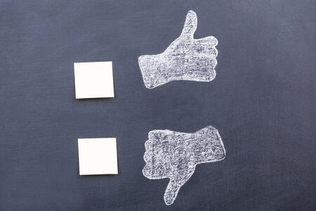 THUMBS DOWN: Yes or no? Blackboard drawing of thumbs up and down with adhesive notes near them