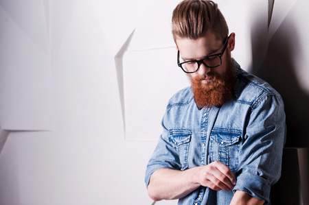 attractive male: Being attentive the small details. Handsome young bearded man wearing glasses and rolling up sleeves