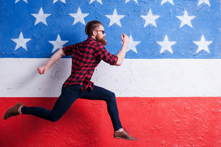 hurrying: Hurrying to be in trend. Handsome young bearded man wearing sunglasses and running along American flag Stock Photo