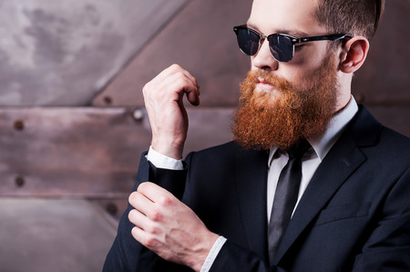 his shirt sleeves: Making business look good. Close-up of a confident young man in shirt and tie adjusting his sleeves Stock Photo