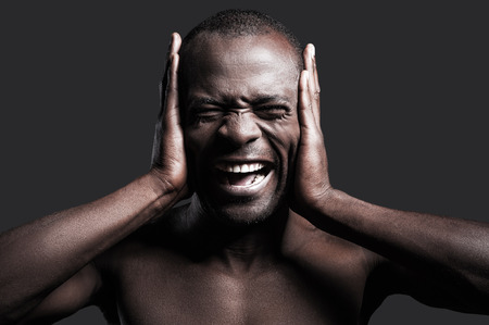 nude male body: Too loud sound. Portrait of young shirtless African man covering ears with hands and shouting while standing against grey background