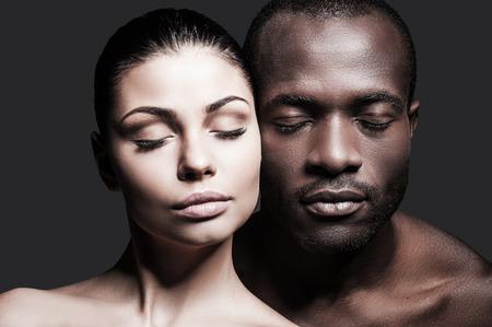 Cara a cara. Retrato de hombre africano sin camisa y la mujer caucásica unir sus rostros el uno al otro y mantener los ojos cerrados mientras está de pie contra el fondo gris Foto de archivo - 33368893