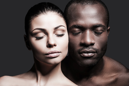 Oog in oog. Portret van shirtless Afrikaanse man en blanke vrouw verlijmen van hun gezichten naar elkaar en houden van de ogen gesloten terwijl staande tegen een grijze achtergrond