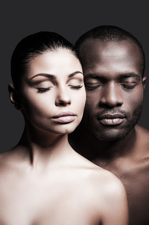 naked black men: One love. Shirtless African man and Caucasian woman bonding their faces to each other and keeping eyes closed while standing against grey background Stock Photo