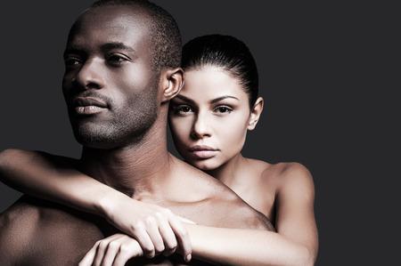 Hij is mijn man. Mooie blanke vrouw binding aan knappe Afrikaanse man en kijken naar de camera terwijl zowel staande tegen de grijze achtergrond