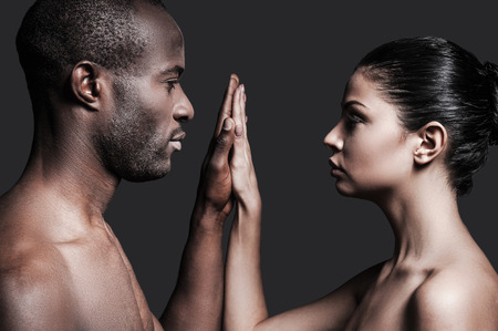 naked couple: One touch and one love. Portrait of shirtless African man and Caucasian woman holding their hands clasped and looking at camera while standing against grey background