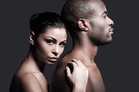 young couple sex: He is absolutely mine. Beautiful Caucasian woman bonding to back of handsome African man and looking at camera while both standing against grey background