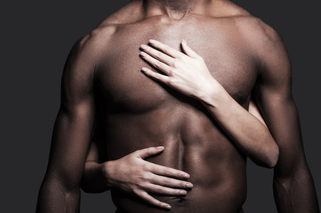 naked black men: Loving this body. Close-up of shirtless African man with female hands embracing his torso against grey background