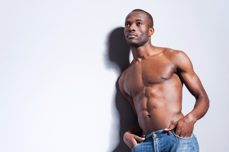 sex symbol: Confidence and masculinity. Handsome young shirtless African man looking away and holding hands in pockets while leaning at the grey wall Stock Photo