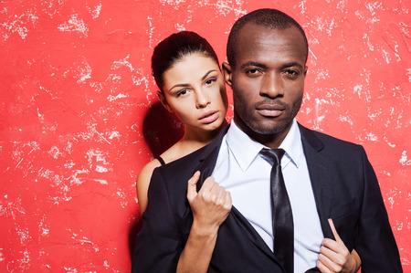 man and woman sex: Высвобожденная желание. Красивый молодой человек в Formalwear стоя красном фоне в то время как женщина, снимая куртку
