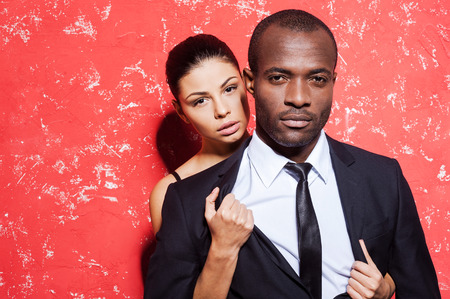 sex symbol: Unleashed desire. Handsome young man in formalwear standing against red background while woman taking off his jacket