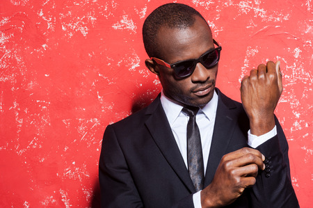model male: Everything should be perfect. Serious young African man in formalwear and sunglasses adjusting his sleeve while standing against red background