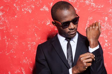 mannequin africain: Tout doit �tre parfait. Serious jeune homme africain en tenues de soir�e et lunettes de soleil de r�glage sa manche tout en se tenant sur fond rouge