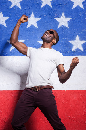 outstretched arms: The happiest in the world! Happy young African man in sunglasses raising his arms up and smiling while standing against American flag Stock Photo