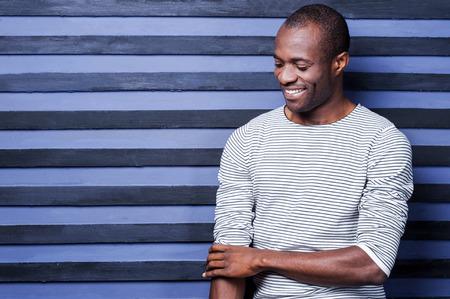 완벽하게 보았습니다. 행복 한 젊은 아프리카 남자 그의 소매를 조정 하 고 줄무늬 배경에서 서있는 동안 웃 고