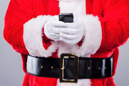 Santa Claus texting. Close-up of Traditional Santa Claus holding mobile phone while standing against grey background photo