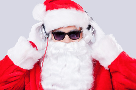 Cool Santa. Santa Claus in sunglasses adjusting his headphones while standing against grey background photo