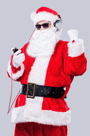 Listening to the Christmas music. Santa Claus in sunglasses and headphones listening to MP3 Player and gesturing while standing against grey background photo