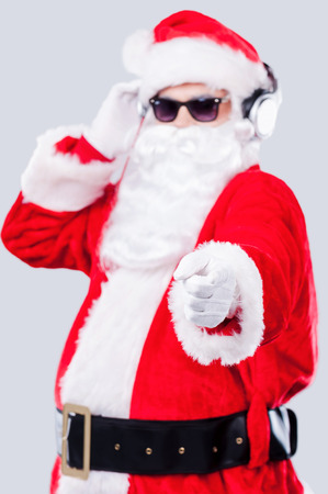 Merry Christmas to you! Cool Santa Claus in sunglasses adjusting his headphones and pointing you while standing against grey background photo