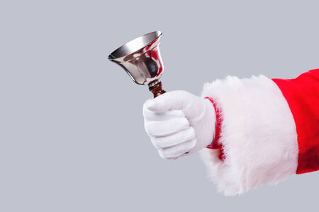 Jingle bells! Close-up of Santa Claus holding metal bell in his hand and against grey background Stock Photo