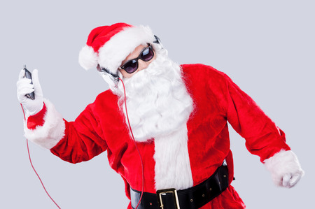 Christmas fun. Santa Claus in sunglasses and headphones listening to MP3 Player and dancing while standing against grey background photo