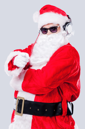 Merry Christmas to you! Santa Claus in sunglasses and headphones pointing you while standing against grey background photo