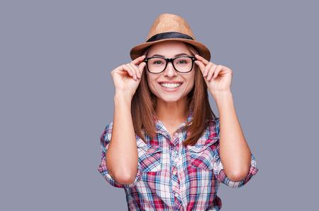 mulher: Beleza estilo funky. Retrato de mulher bonita em óculos e chapéu badalado ajustando os óculos e sorrindo em pé contra um fundo cinza