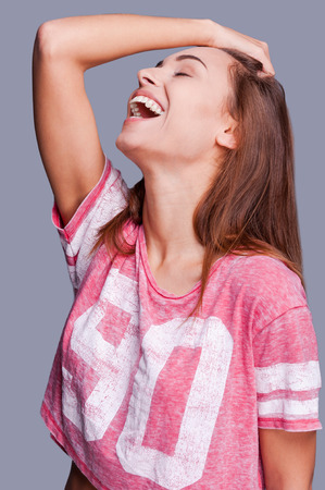longer: More laugh longer life. Attractive young woman in funky wear holding her hand in hair keeping eyes closed