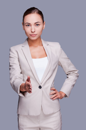 shaking out: Welcome on board! Confident young businesswoman stretching out hand for shaking while standing against grey background