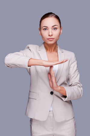 stop time: Time out! Confident young businesswoman gesturing time out  sign while standing against grey background Stock Photo