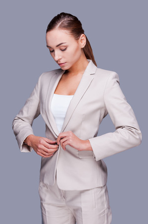 buttoning: Bossy and stylish. Confident young businesswoman buttoning his jacket while standing against grey background