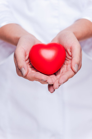 Taking good care of your heart. Close-up of female doctor in white uniform holding heart prop photo