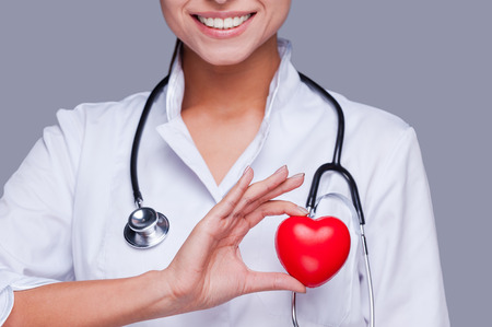 In love with her profession. Close-up of female doctor in white uniform holding heart prop and smiling Фото со стока
