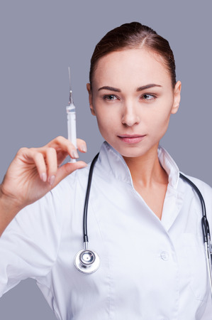 injection woman: The benefit of medical advances. Confident female doctor in white uniform holding syringe and looking at it while standing against grey background